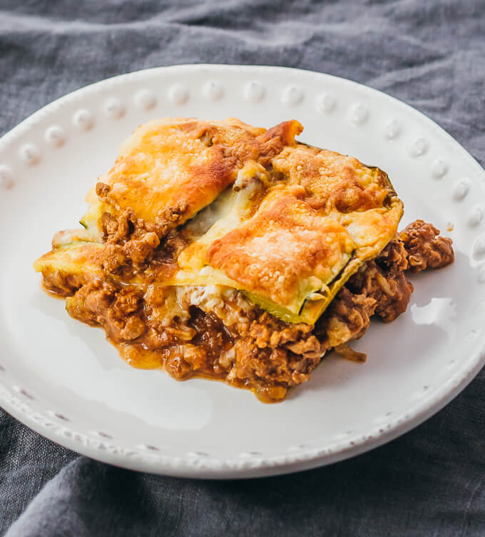 Single serving of healthy sliced zucchini lasagna on a white plate