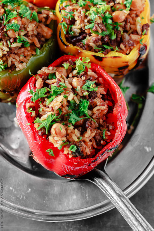 Mediterranean Stuffed Peppers Recipe | The Mediterranean Dish. Easy, delicious, stuffed peppers recipe with step-by-step tutorial. The gluten free Mediterranean-style stuffing with rice, chickpeas and spiced ground beef is a favorite! See the full recipe on TheMediterraneanDish.com