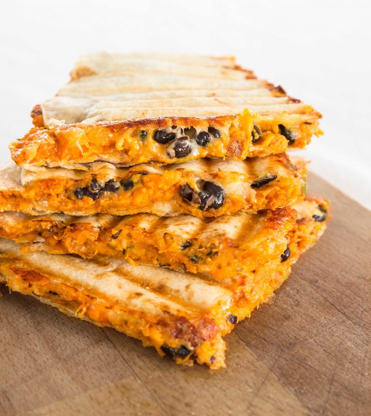 Stacked Roasted Sweet Potato and Black Bean Quesadillas on chopping board