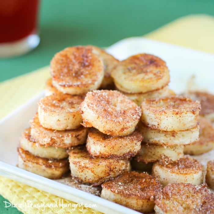 Front view of pan fried cinnamon bananas stacked in columns and rows on a white plate