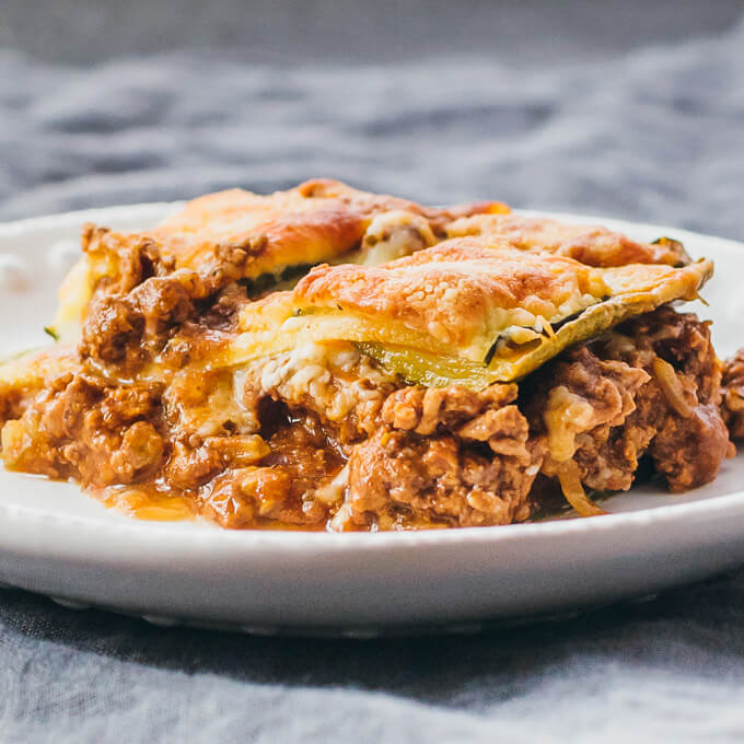 Single serving of low carb zucchini lasagna with meat sliced and served on a white plate