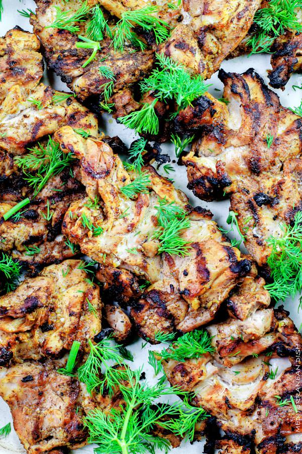 Mediterranean Grilled Chicken + Dill Greek Yogurt Sauce. Top grill recipe! Marinate boneless chicken thighs in Mediterranean spices, olive oil and lemon juice. Grill for less than 15 minutes, and serve with this flavor-packed dill yogurt sauce! Pin it to try soon!